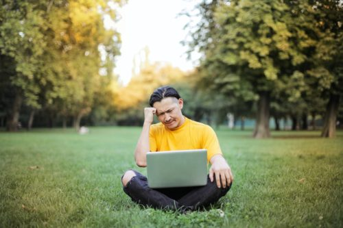 man-in-yellow-crew-neck-t-shirt-using-silver-macbook-on